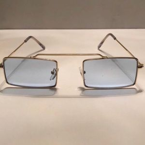 Light blue lens sunglasses. Gold metal frame.